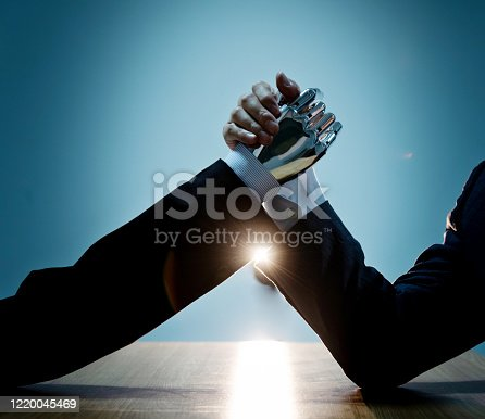 1050855372 istock photo Businessman hand and robot doing arm wrestling 1220045469