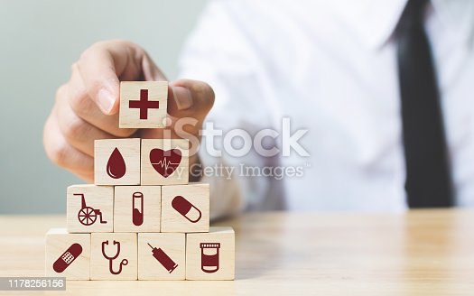 1029077176istockphoto Businessman hand arranging wood block stacking with icon healthcare medical, Insurance for your health concept 1178256156
