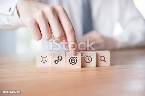 istock Businessman hand arranging wood block with icon business strategy and planning 1030145712