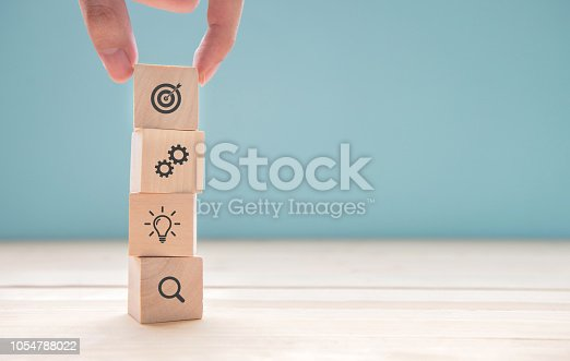 istock Businessman hand arranging wood block with icon business strategy and Action plan. 1054788022