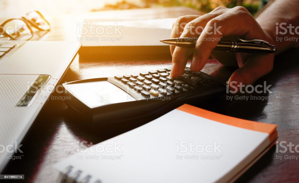 Businessman hand calculate bout cost with laptop for search data. stock photo