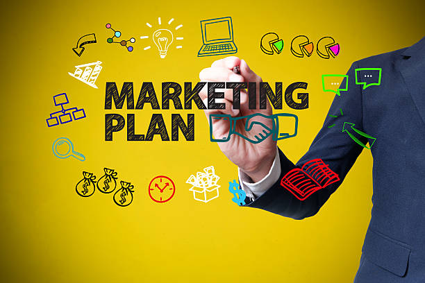 businessman hand drawing and writing MARKETING PLAN on yellow stock photo