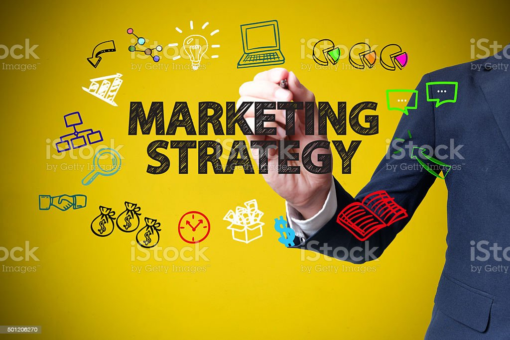 businessman hand drawing and writing MARKETING STRATEGY stock photo