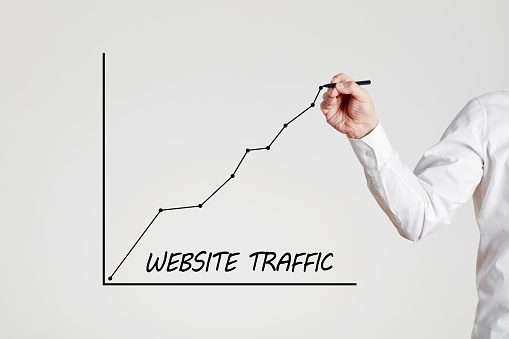 Businessman hand draws a rising line graph with the word website traffic. Increasing website traffic concept.