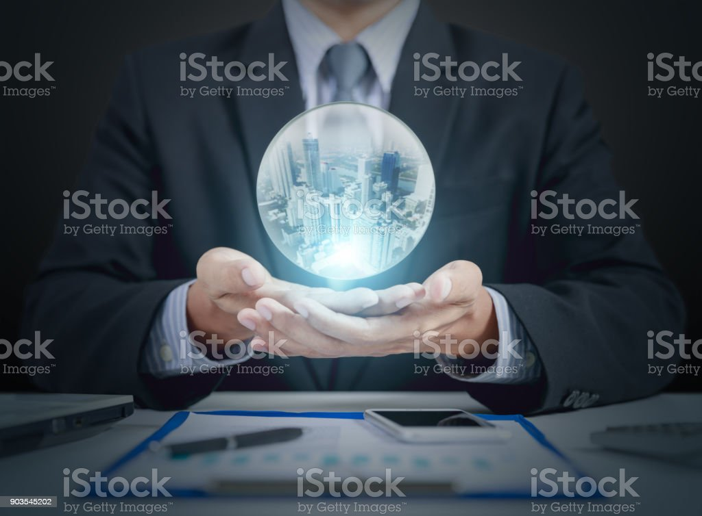 businessman hand hold crystal ball with building inside stock photo