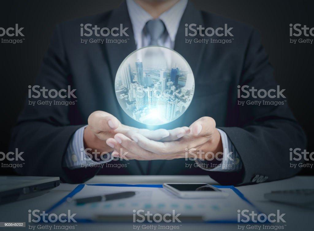 asimiento de la mano del empresario bola de cristal con edificio dentro - foto de stock