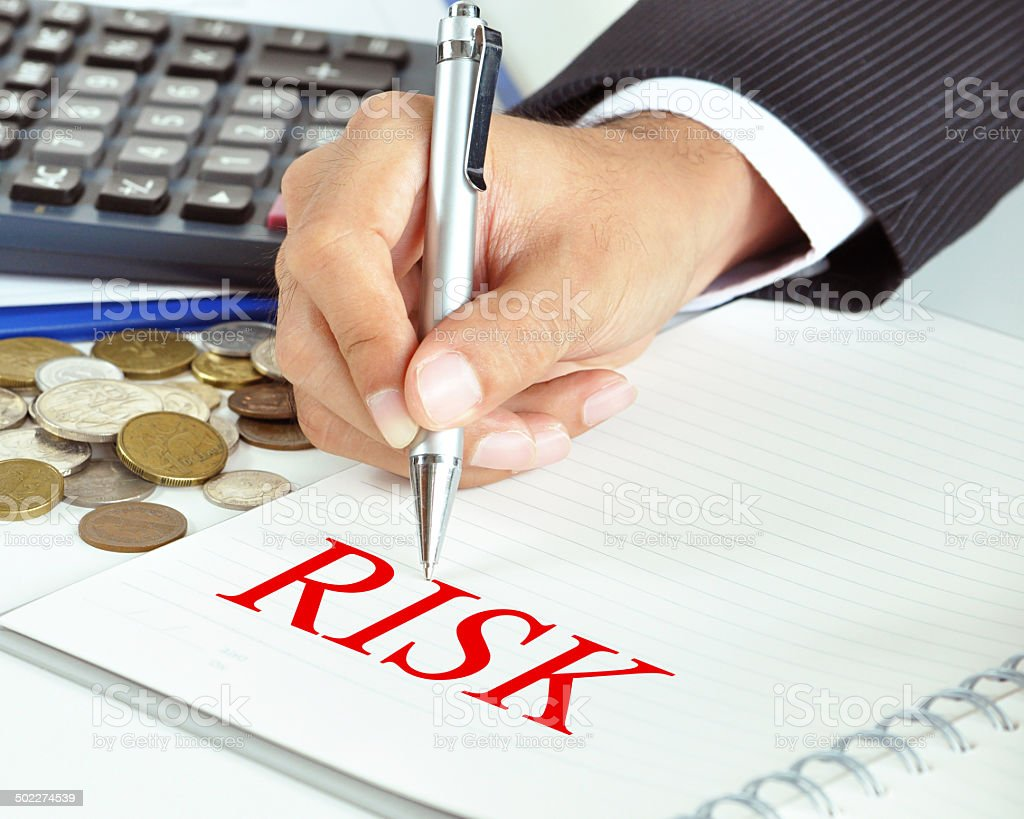 Businessman hand holding a pen pointing to RISK word stock photo