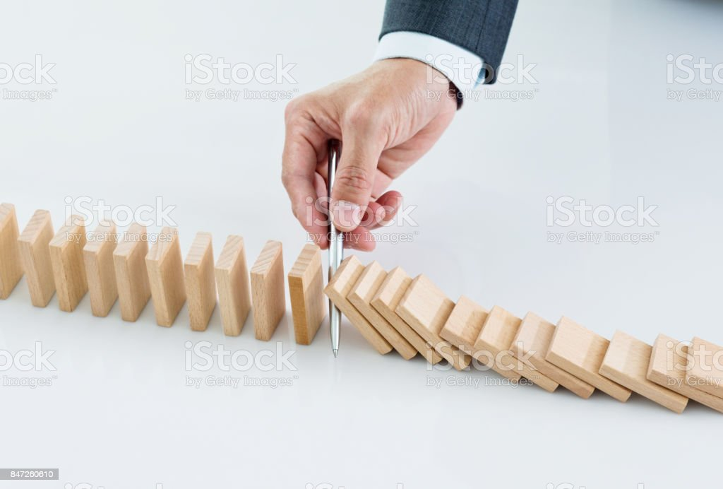 Technology Management Image: Businessman Hand Holding A Pen Stop Domino Effect Stock