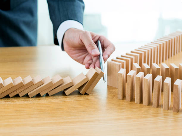 Businessman hand holding a pen stop domino effect stock photo