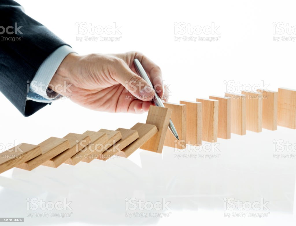 Businessman hand holding a pen stop domino effect.