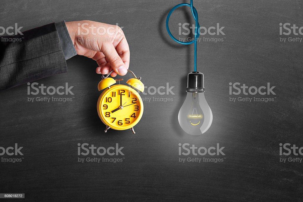 Businessman hand holding alarm clock with hanging lightbulb stock photo
