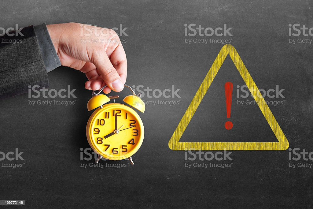 Businessman hand holding alarm clock with warning sign stock photo