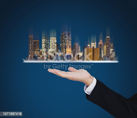684793898 istock photo Businessman hand holding digital tablet with modern buildings hologram. Smart city, building technology and real estate business 1071597416