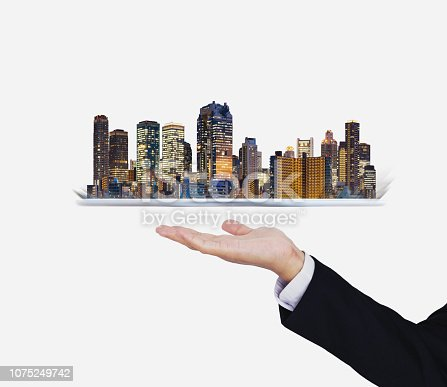 684793898 istock photo Businessman hand holding digital tablet with modern buildings hologram. Smart city, building technology and real estate business 1075249742