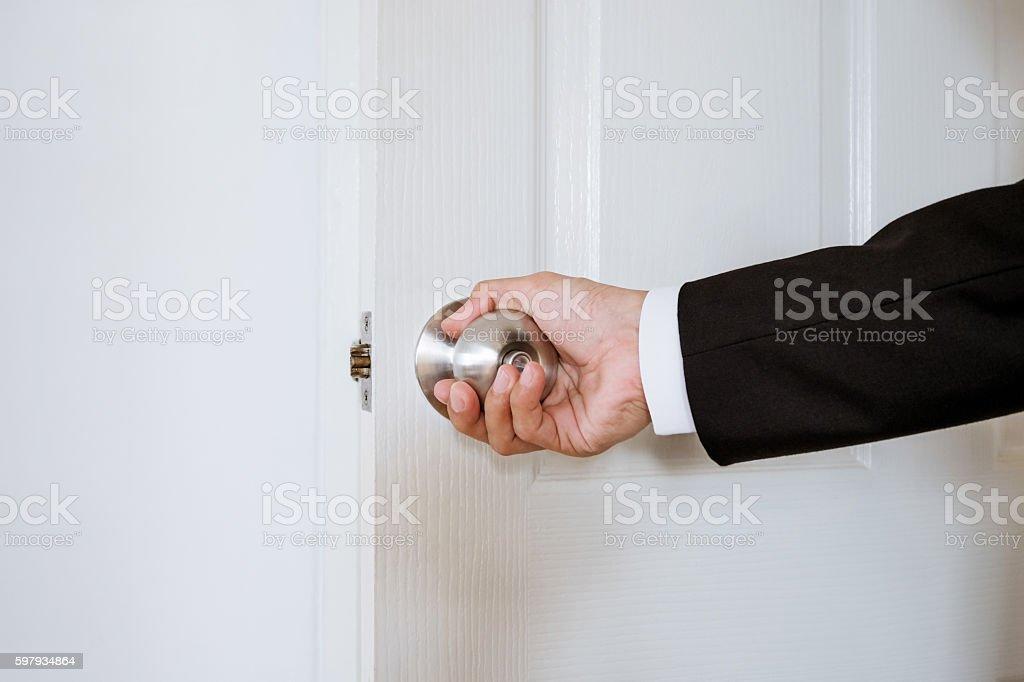 Businessman hand holding door knob, opening or closing door stock photo