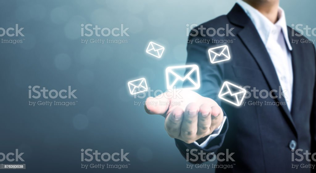 Businessman hand holding e-mail icon, Contact us by newsletter email and protect your personal information from spam mail concept stock photo