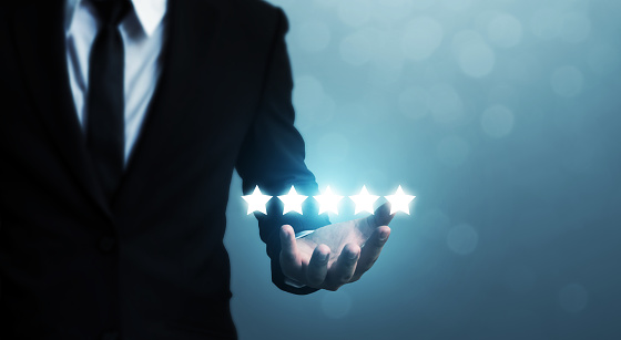 917079212 istock photo Businessman hand holding five star symbol to increase rating of company concept 1066475908
