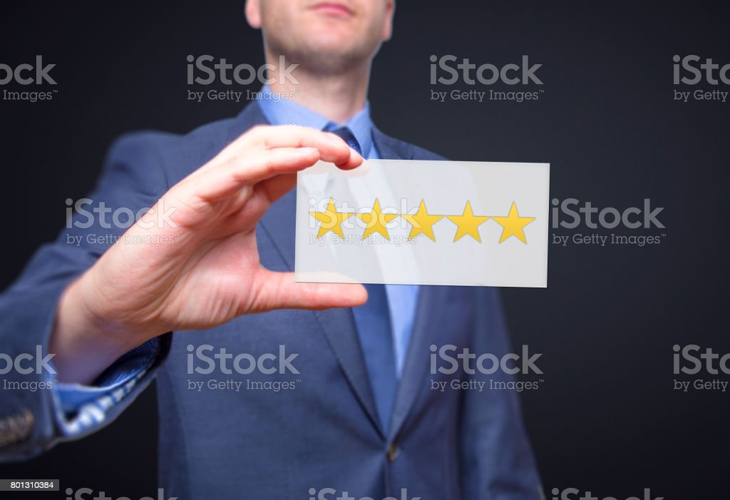 Businessman hand holding five stars isolated on black background. Business rating concept. Stock Photo stock photo