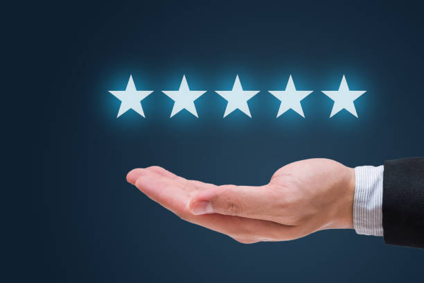 Businessman hand holding five stars isolated on blue background stock photo