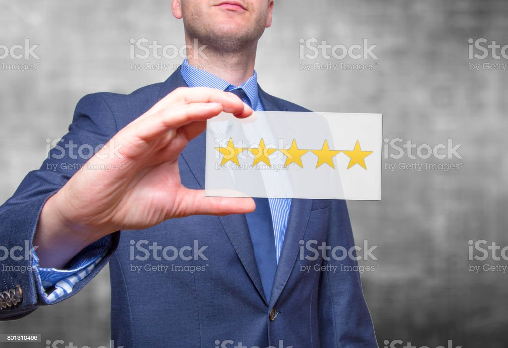 Businessman hand holding five stars isolated on grey background. Business rating concept. Stock Photo stock photo