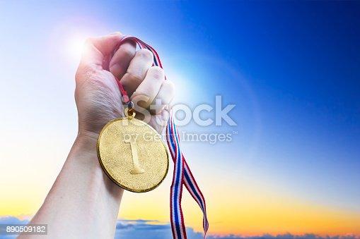 istock Businessman hand holding golden coin medal. 890509182
