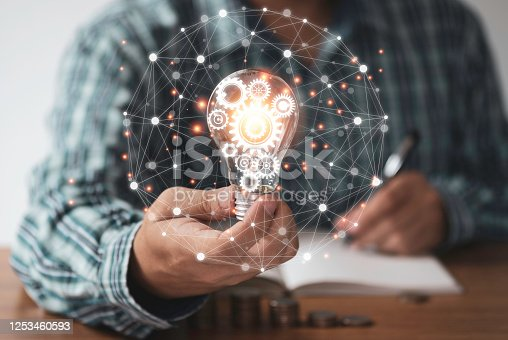 637573406 istock photo Businessman hand holding lightbulb with orange glowing and connection line. Creative thinking idea concept. 1253460593