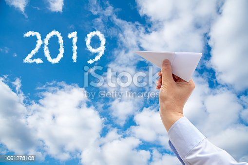 istock Businessman hand holding paper plane on sky Background. 1061278108