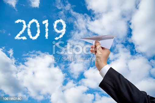 istock Businessman hand holding paper plane on sky Background. 1061950180