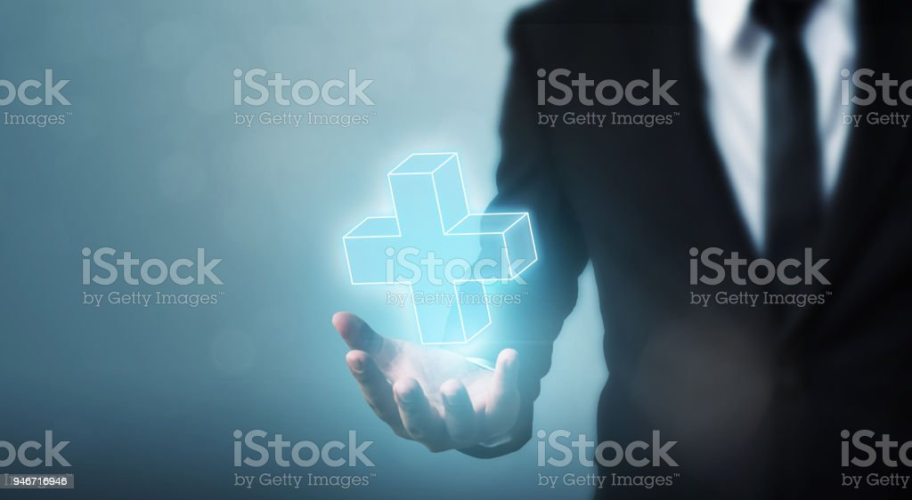 Businessman hand holding plus sign virtual means to offer positive thing (like benefits, personal development, social network) stock photo