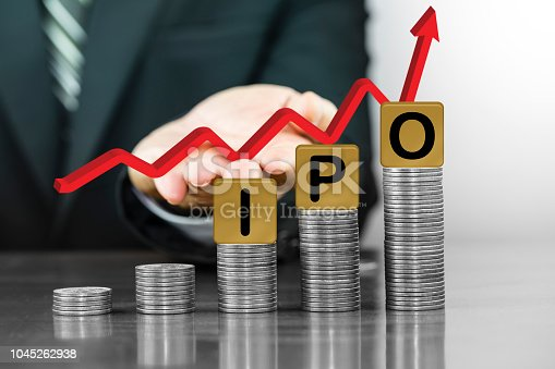 istock Businessman hand holding red arrow up with the letters IPO on money coin stack arranged as a graph 1045262938