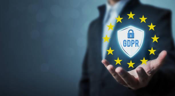 Empresario sosteniendo firmar Reglamento de protección de datos generales (GDPR) de la mano y el escudo con el icono de llave - foto de stock
