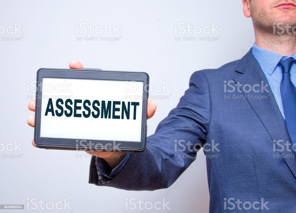 Businessman hand holding tablet with Assessment text sign. Isolated on white. Business concept. Stock photo stock photo
