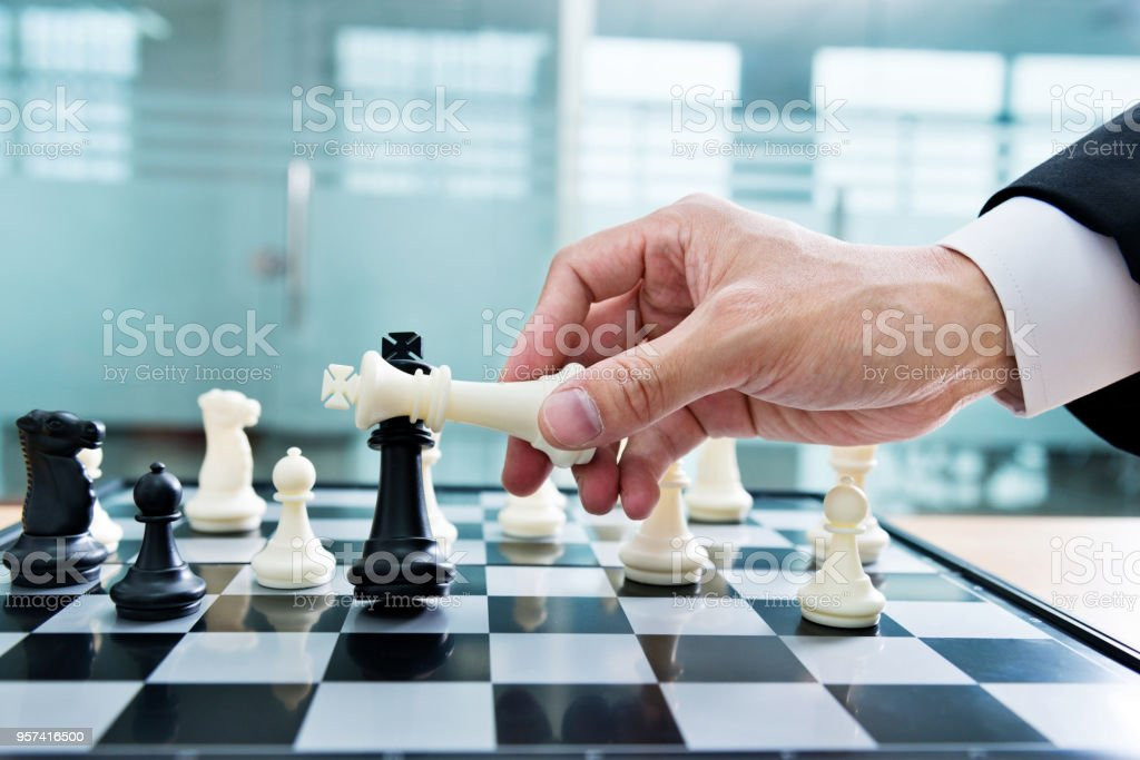 Businessman Hand Holding White Chess Beat Black Royalty Free Stock Photo