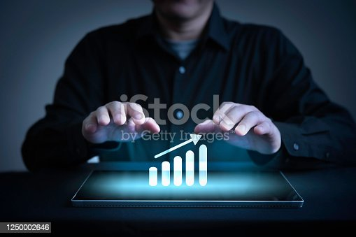 890150646 istock photo Businessman hand on graphic graph growing from digital tablet 1250002646