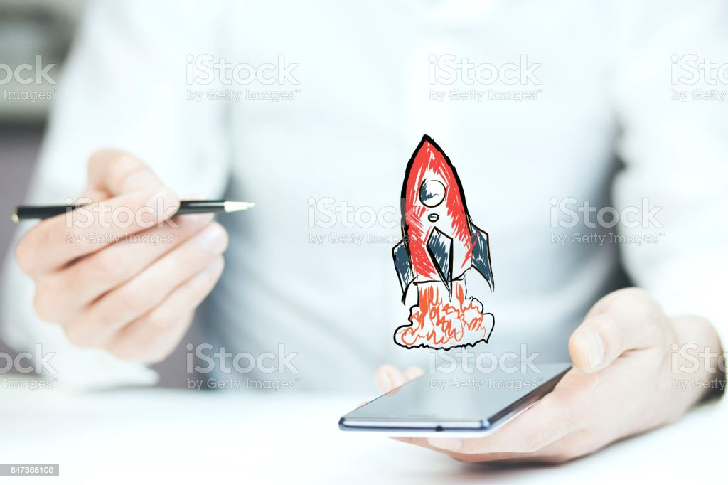 Businessman hand phone with red rocket stock photo