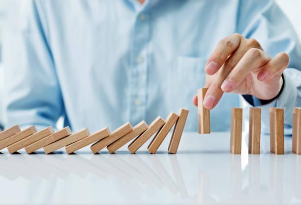Businessman hand pick up one domino stock photo