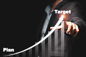 Businessman hand point drawing increase trend arrow and growing chart from plan to target on black background. It is symbol of business investment growth concept.