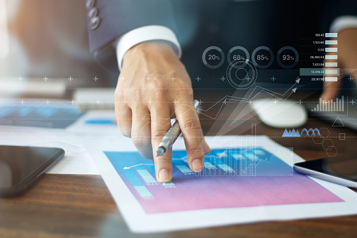 istock Businessman hand pointing at graph chart growth business document 1182604337