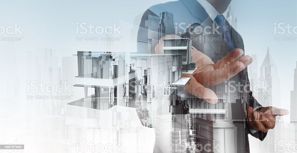 businessman hand presents house model on modern computer stock photo
