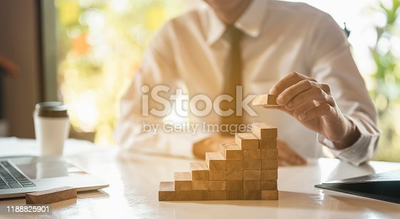 Businessman hand pulling out or placing wood block on the  tower and semi-pyramid in modern office. Plan and strategy in business.