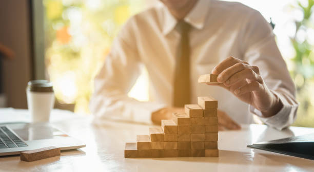 Businessman hand pulling out or placing wood block on the  tower and semi-pyramid in modern office. Plan and strategy in business. Businessman hand pulling out or placing wood block on the  tower and semi-pyramid in modern office. Plan and strategy in business. stable stock pictures, royalty-free photos & images