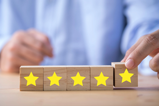 917079212 istock photo Businessman hand putting yellow star which is printed on wooden cube. Customer evaluation survey and satisfaction concept. 1223008327