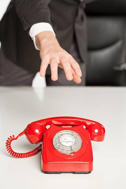 geschäftsmann hand, wenn sie sich für einen klassischen telefon - rot bekümmerte möbel stock-fotos und bilder