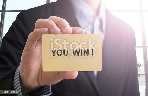 istock Businessman hand show banner you win text. 649163592
