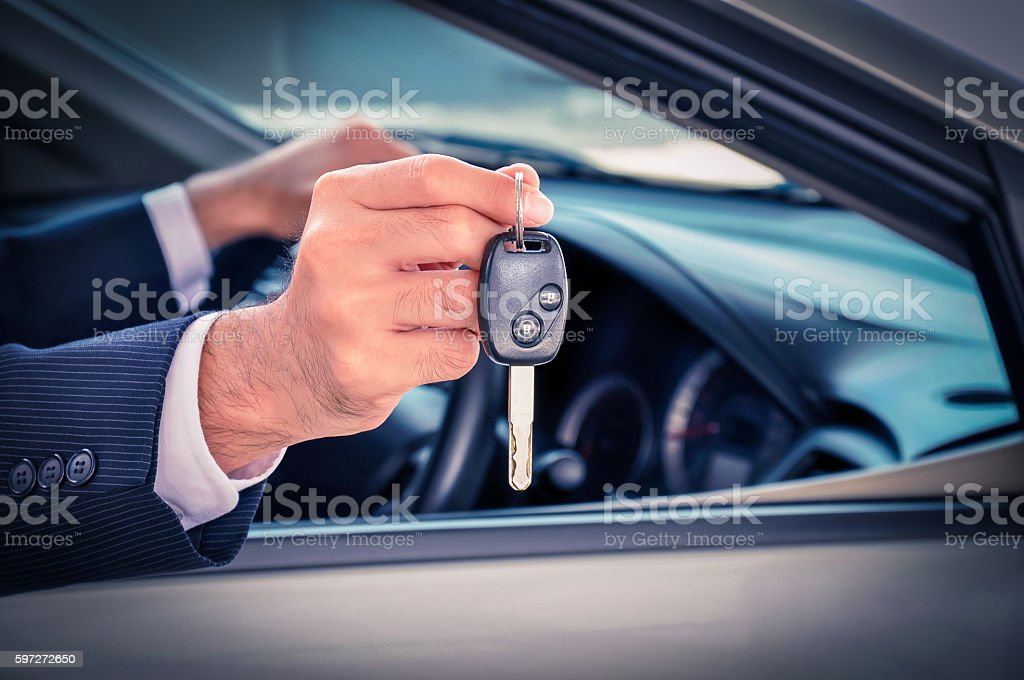 Businessman hand showing a car key royalty-free stock photo
