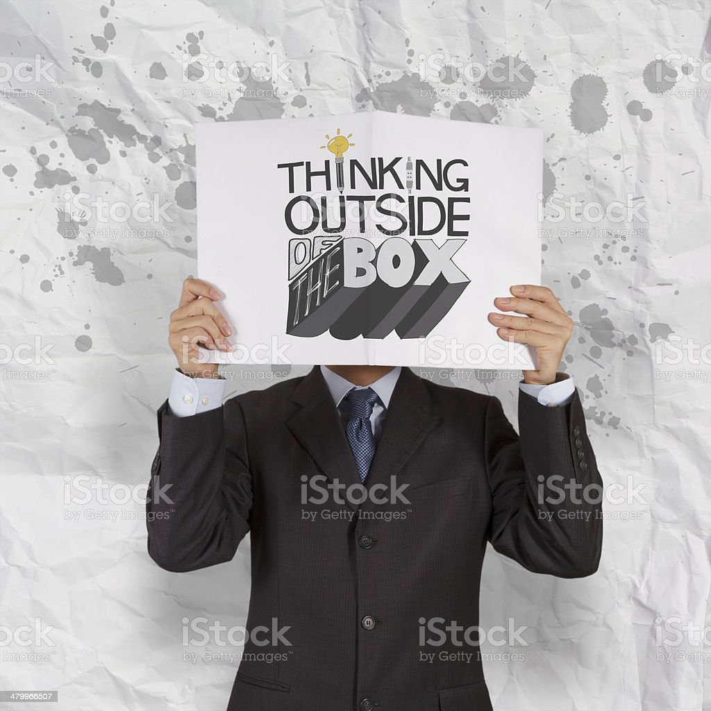 businessman hand showing book of design word THINKING OUTSIDE OF royalty-free stock photo