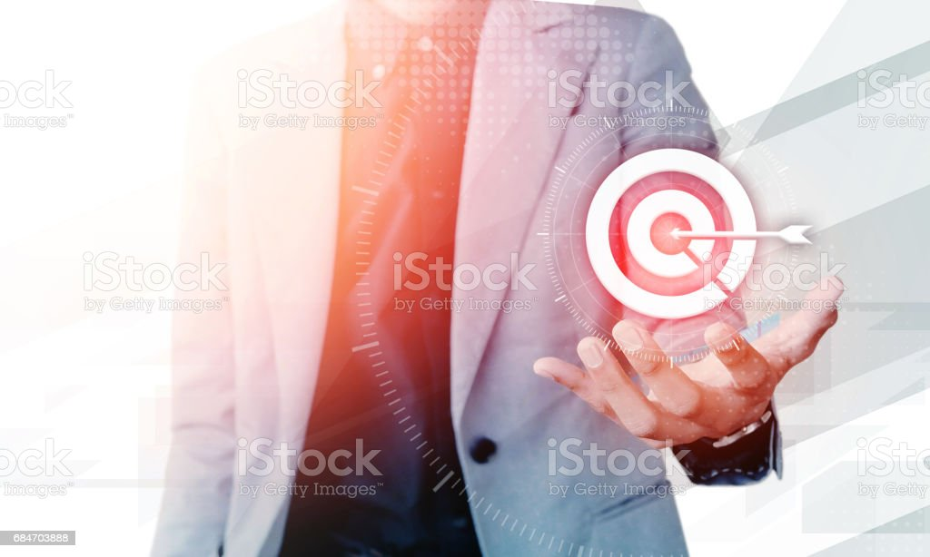 Businessman hand showing on target business concept with blank copyspace area for text or slogan, against grey background stock photo
