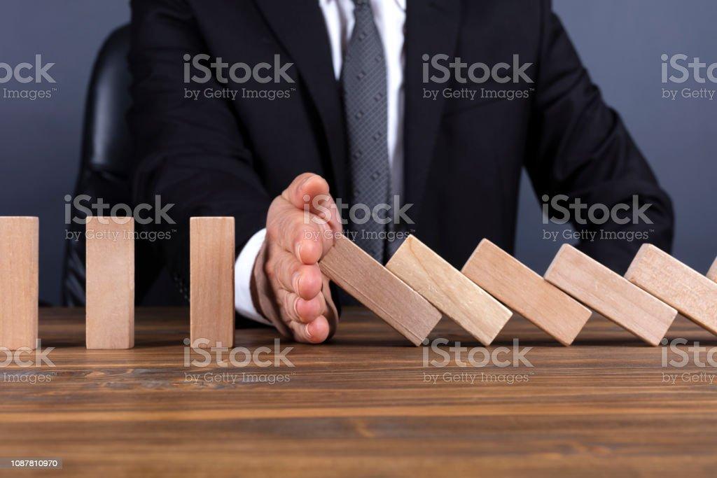 Businessman hand stop domino effect