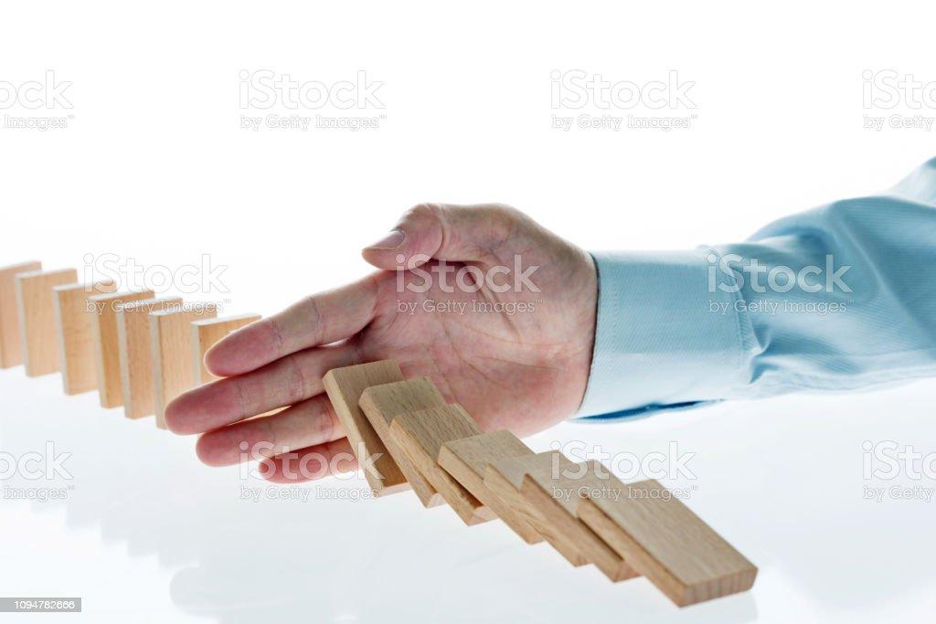 Businessman hand stop domino effect.