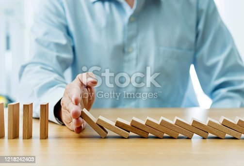 Businessman hand stopping falling blocks on table.